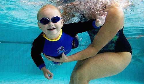 SYDNEY, AUSTRALIA - MARCH 16:  A toddler held by his mother swims underwater during a swimming class for babies at Lane Cove pool March 16, 2007 in Sydney, Australia. As the baby boom in Australia continues, the popularity of swimming classes for babies and toddlers is also on the increase. About 80% of the Australian population live on the coast, with swimming and surfing being major pastimes, leading parents to introduce their kids to water at an early age.    (Photo by Ian Waldie/Getty Images)
