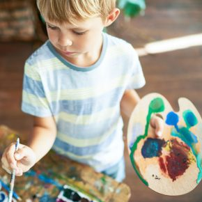 High angle portrait of cute blonde little boy painting on easel during art class, concentrating hard on his masterpiece